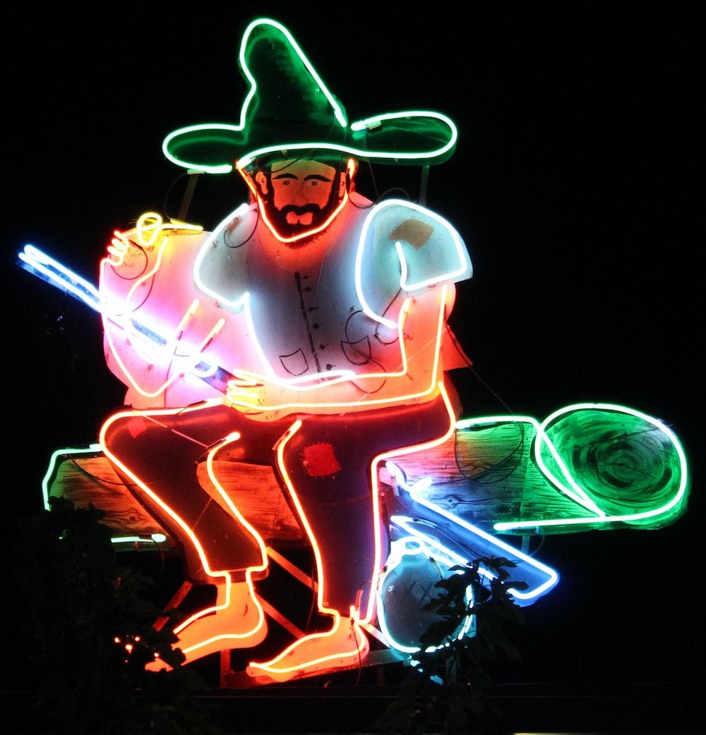 man sitting on log lighted artwork