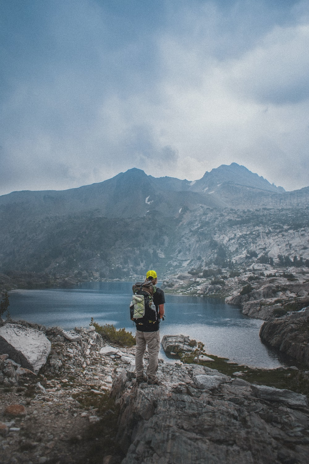 man standing on gray rocky mountain