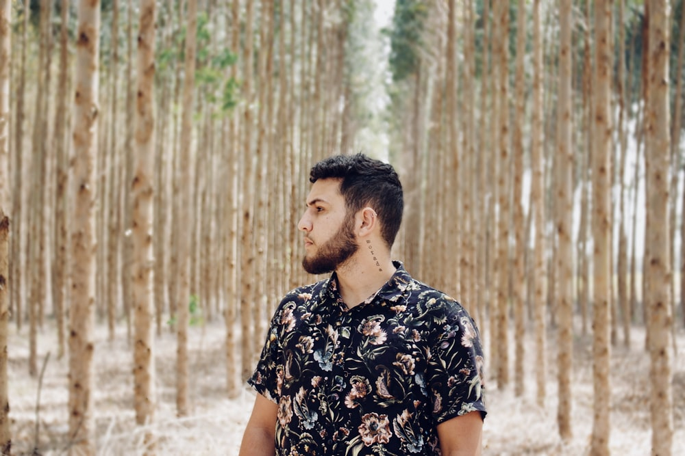 shallow focus photo of man in black and pink floral button-up T-shirt