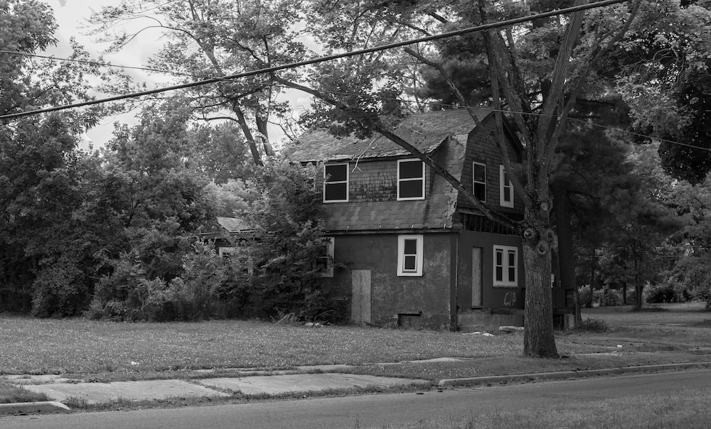 greyscale photo of concrete house surrounded with trees