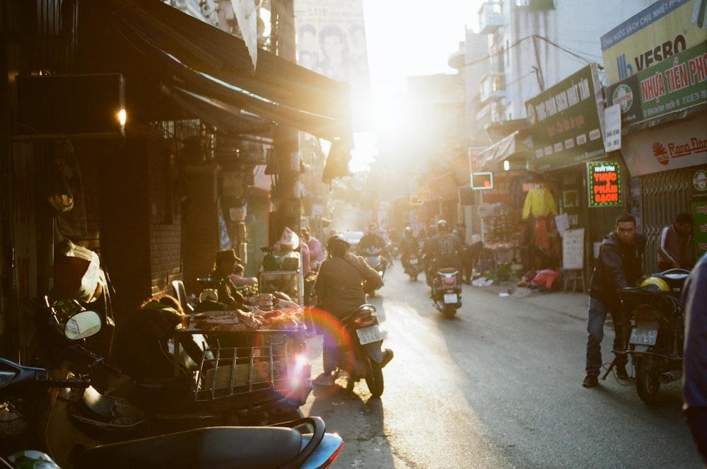 man holding motorcycle on road between buildings