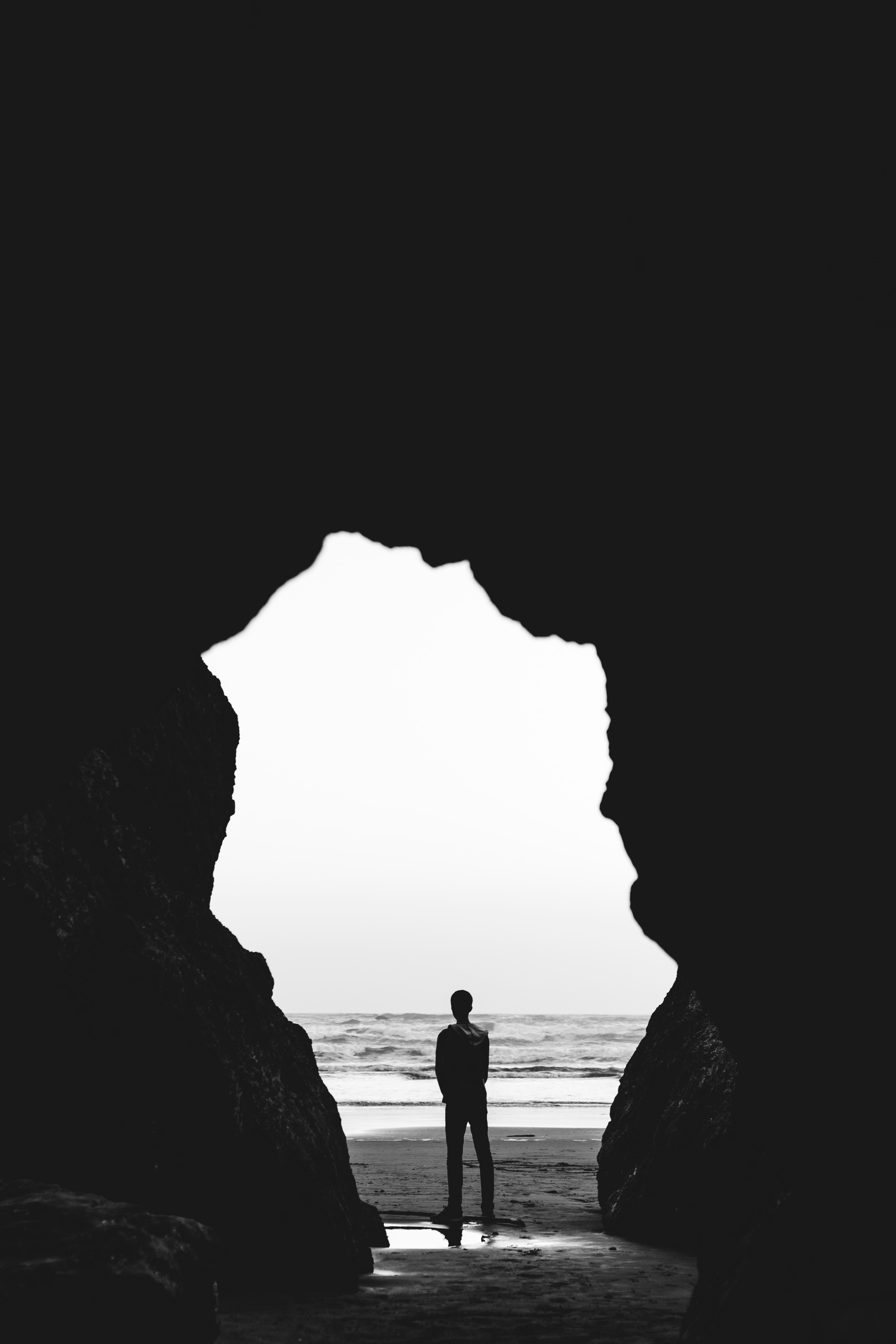 grayscale photography of man standing on seashore