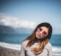 woman with sunglasses on white and beach
