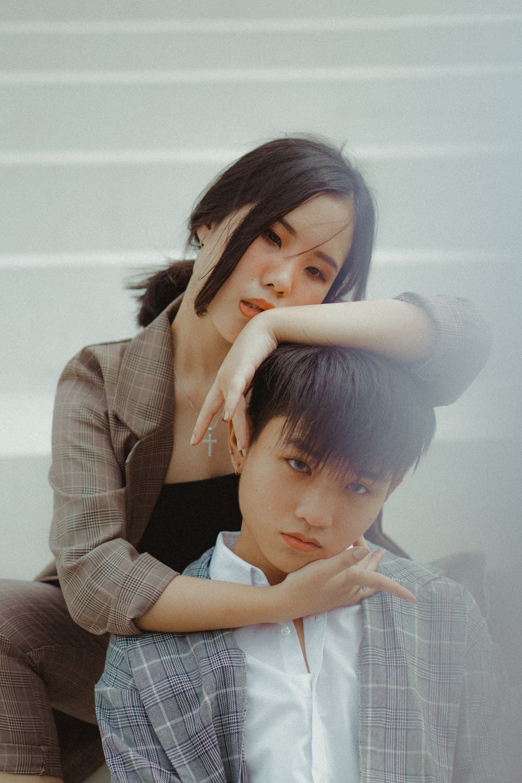 woman holding boy's head near white wall