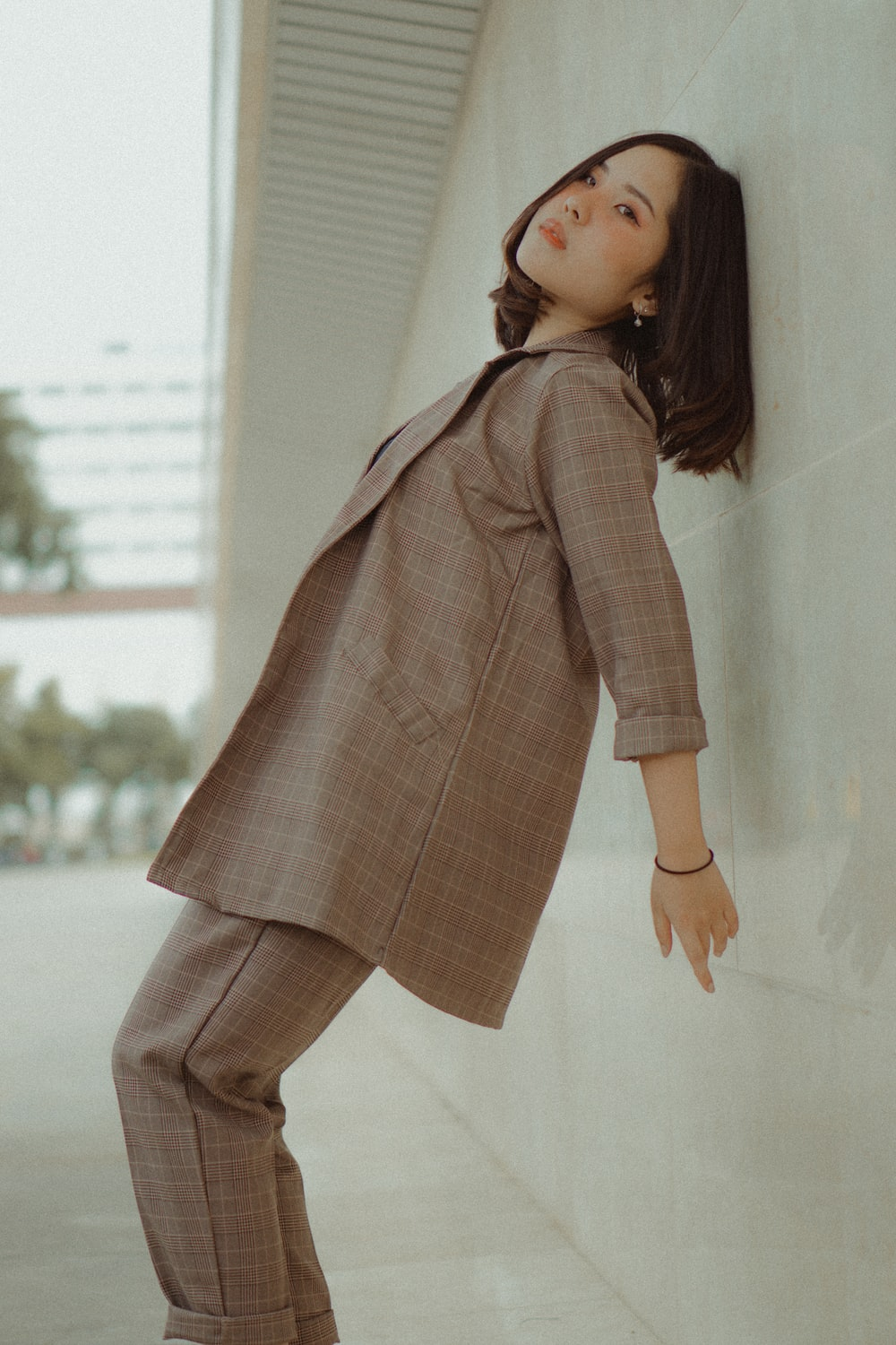 woman wearing brown blazer and pants leaning on wall