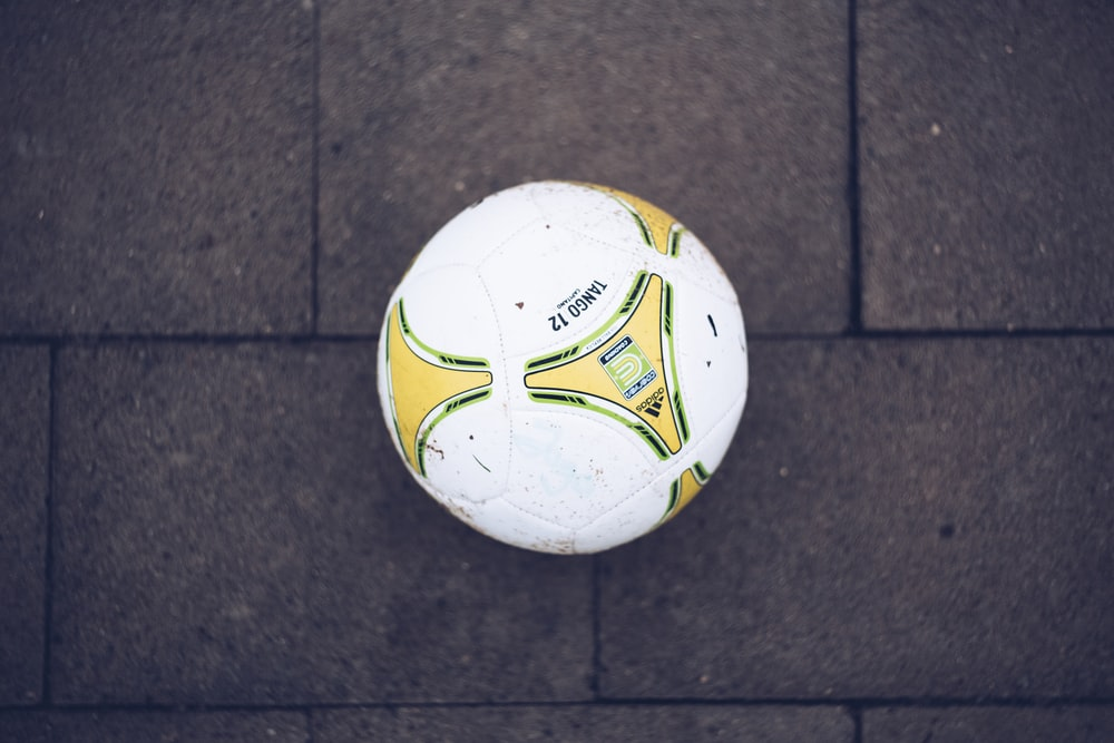 white, yellow, and green soccer ball