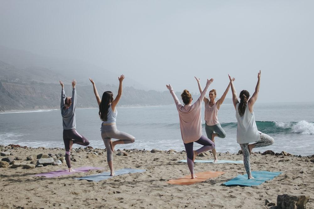 five woman standing on seashore