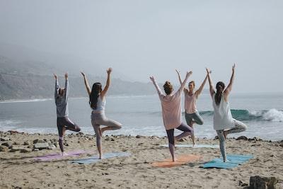 five woman standing on seashore yoga teams background