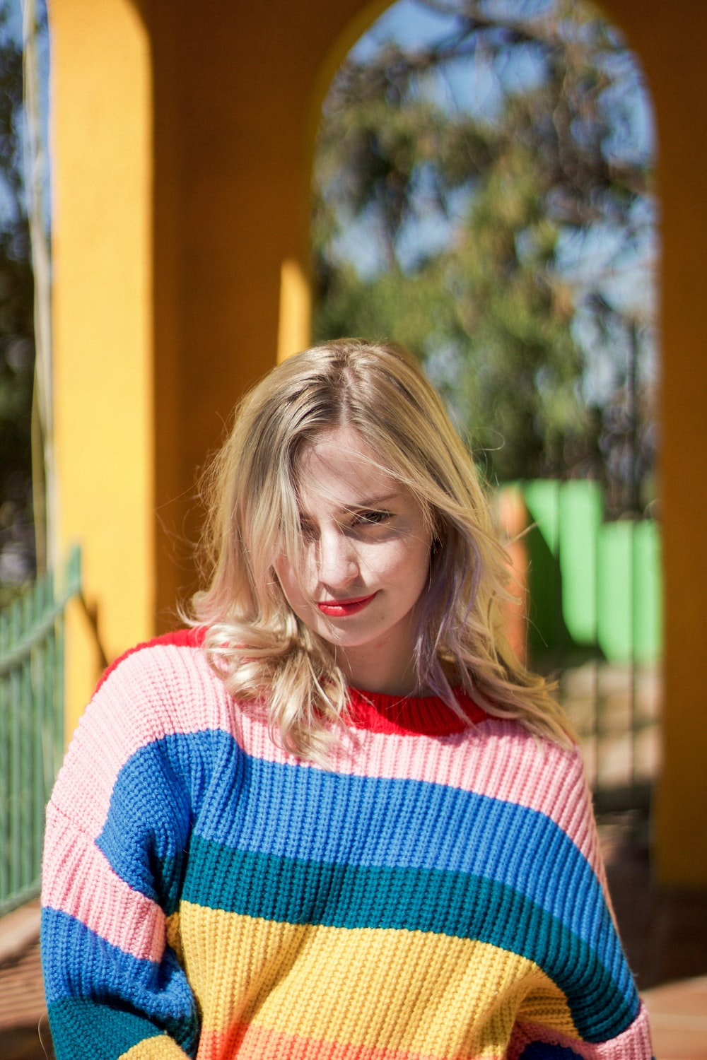 woman in red, pink, blue, and yellow striped knit sweater