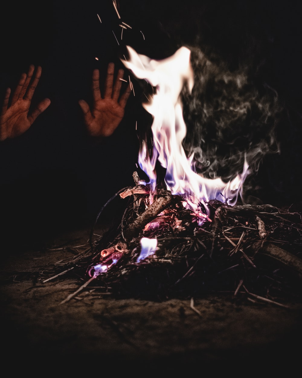 person heating both hands on bornfire