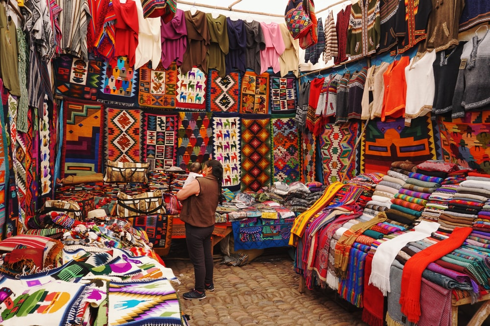 woman in store with display of assorted shirts and textiles