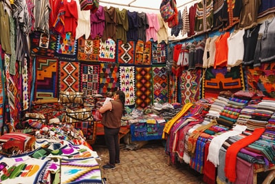woman in store with display of assorted shirts and textiles peru zoom background
