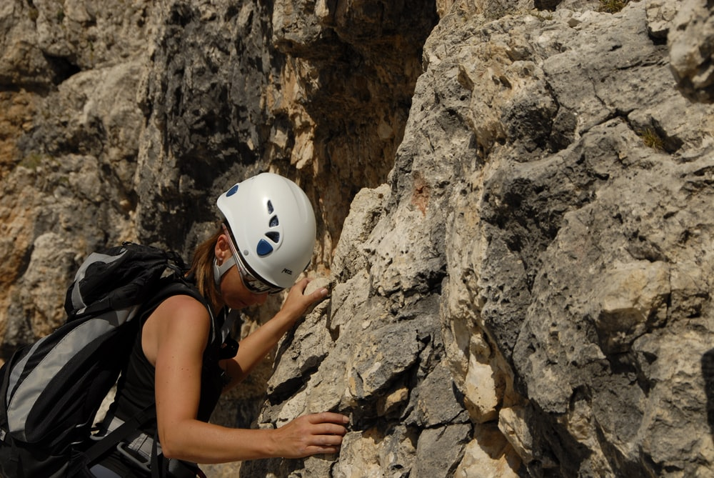 person climbing on rocking mountain