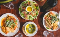 four assorted dishes on wooden surface
