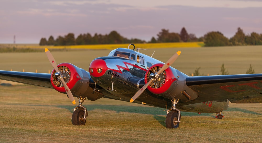 black and red monoplane on green grass field