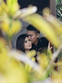 man kissing woman behind plants