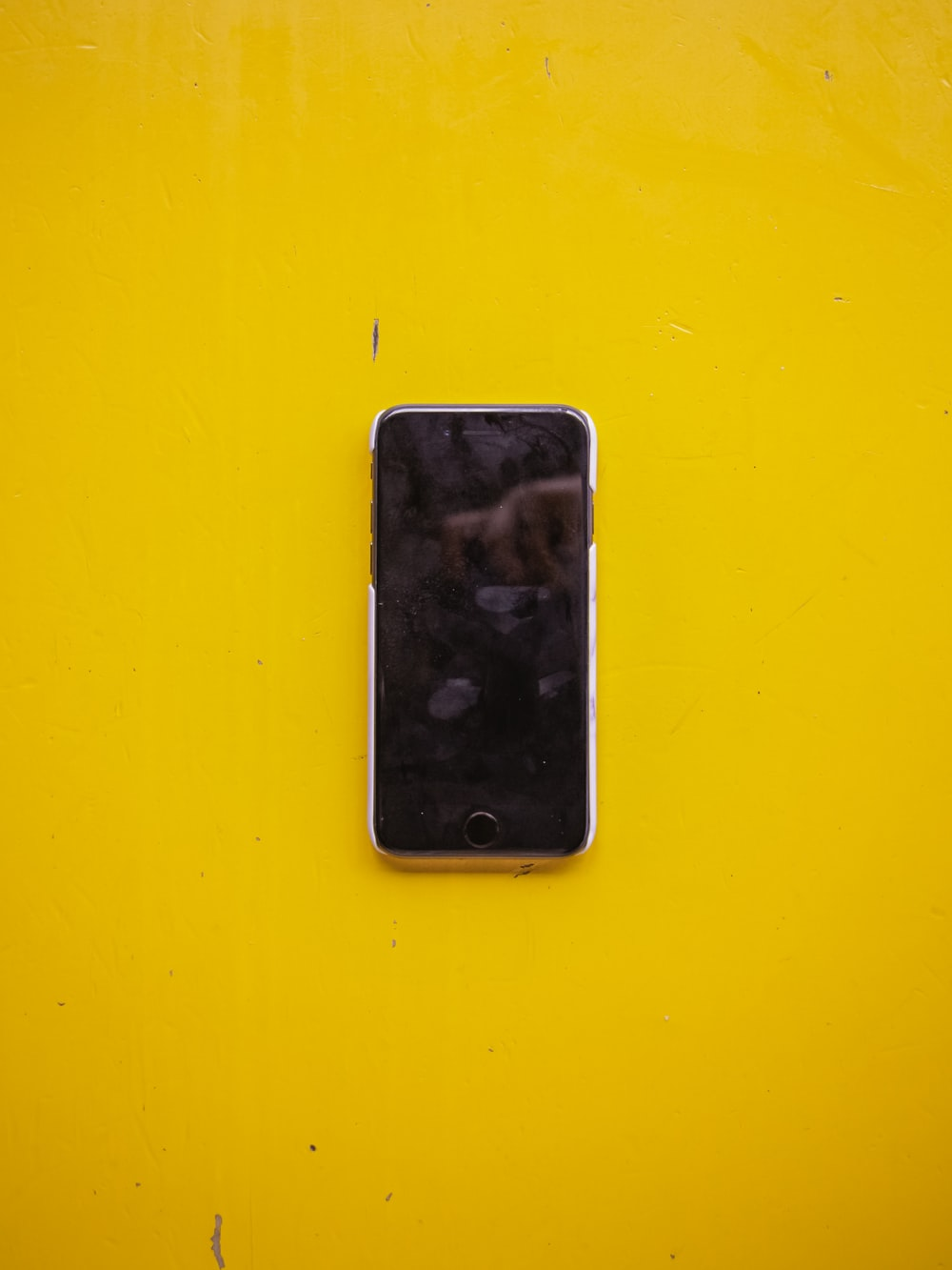 silver iPhone 5 on yellow surface