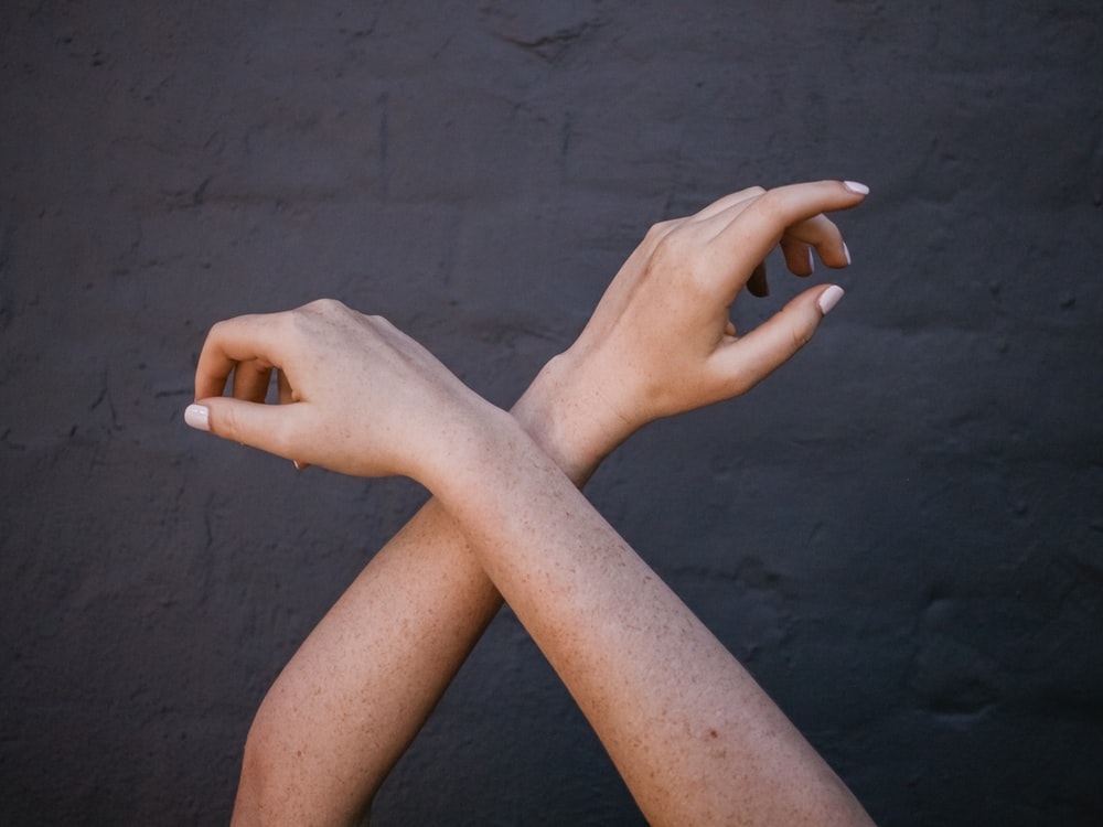 crossed person's arms