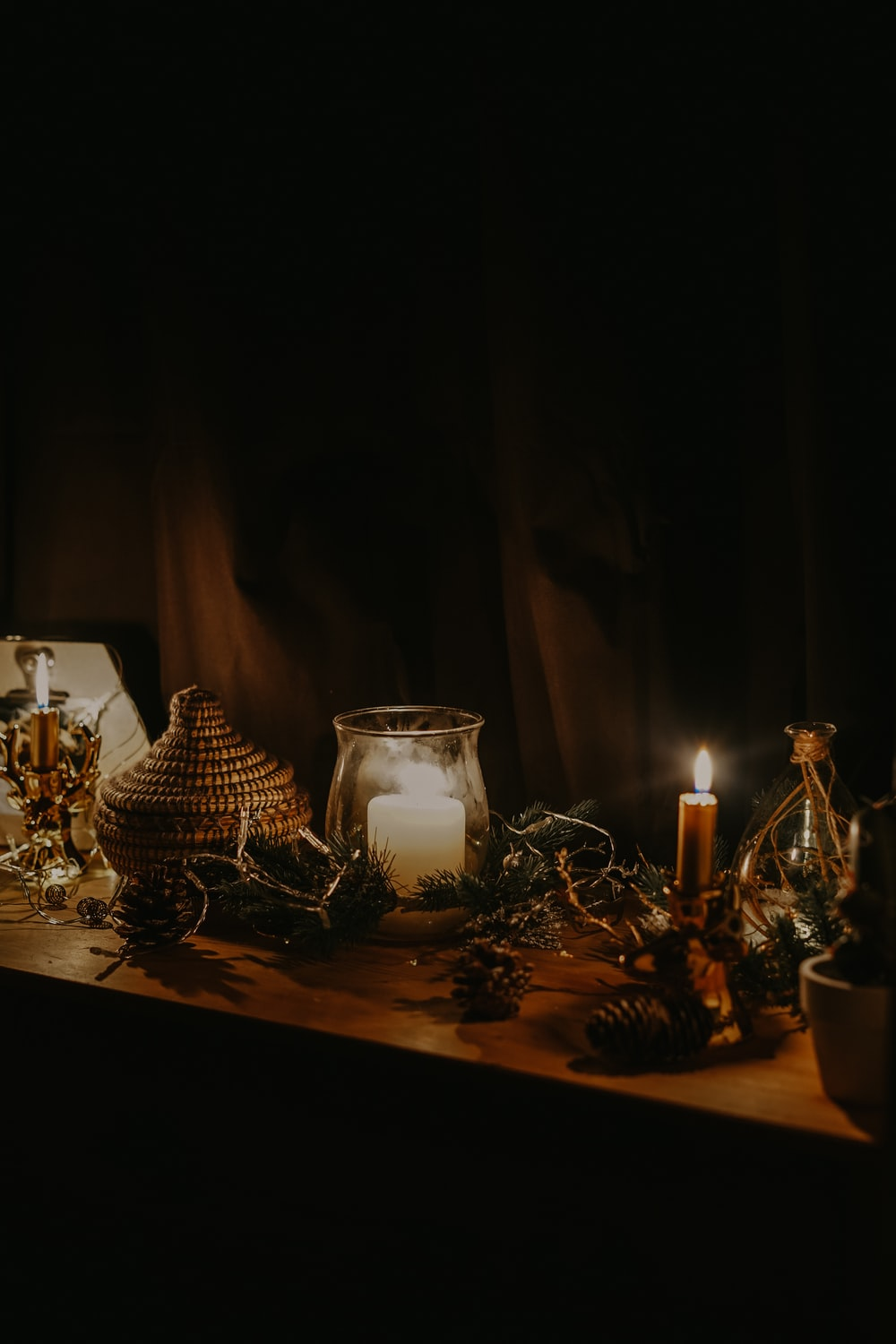 lighted candle near jars and pine cone on table