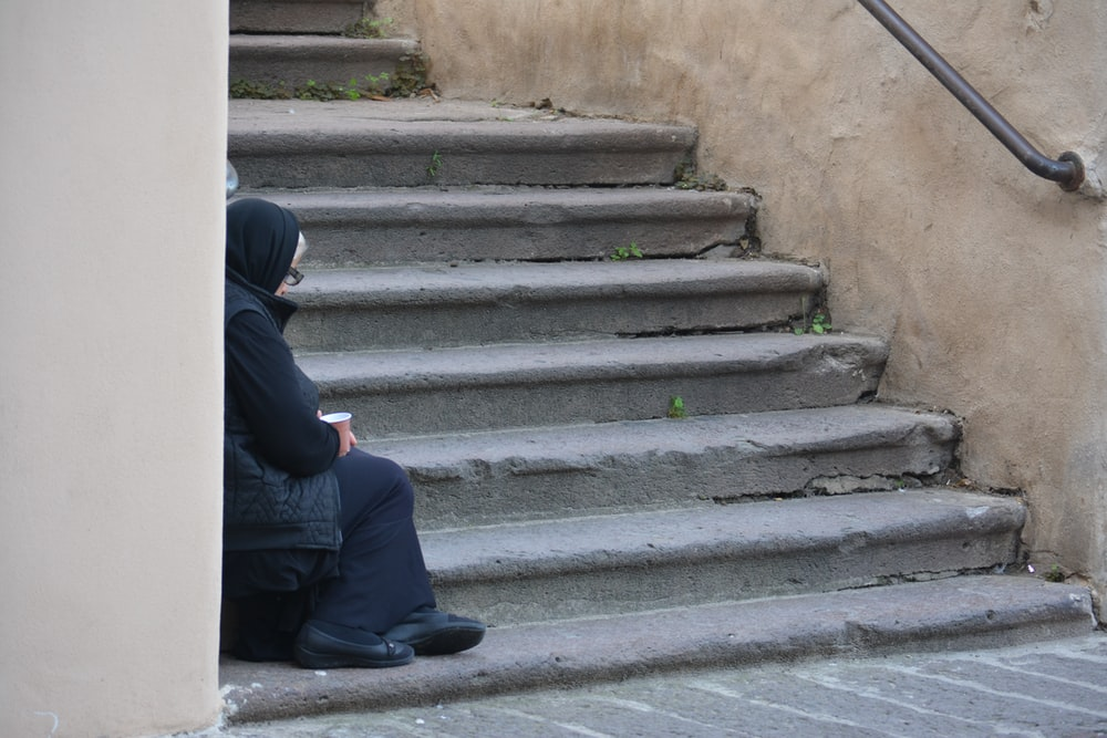 person sitting on stair during daytime