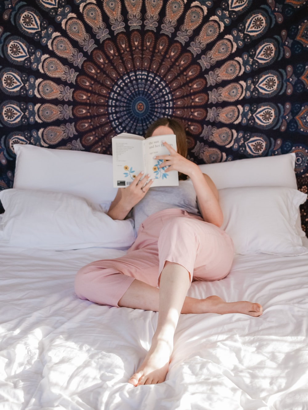 woman lying on bed while reading a book