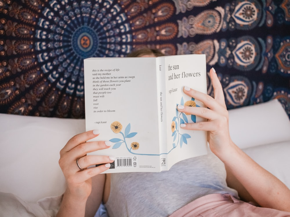 person reading book in bed