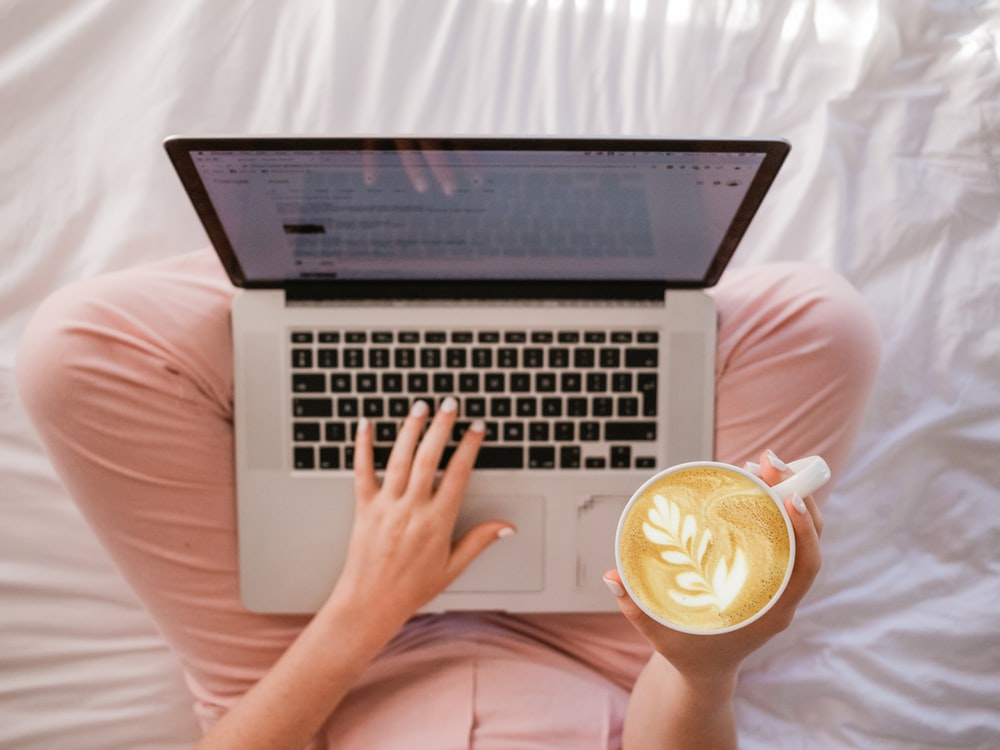 person using MacBook Pro and holding cappuccino
