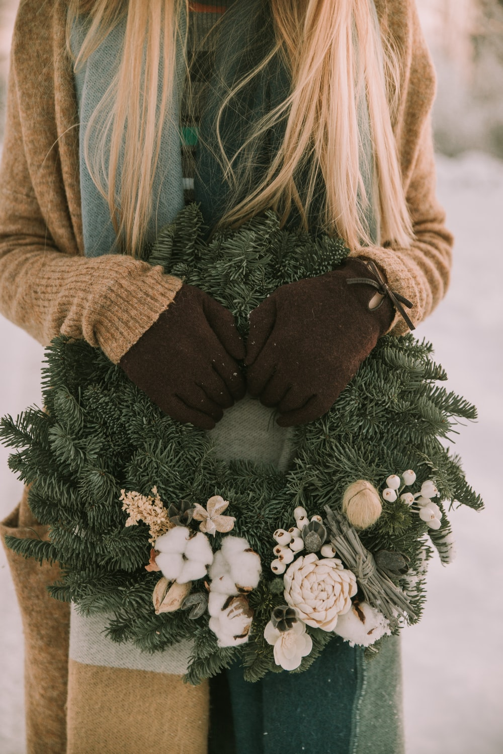 woman holding white and green floral wreath outdoor