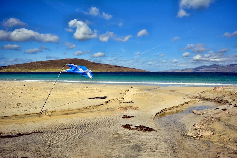 sand near ocean under blue sky
