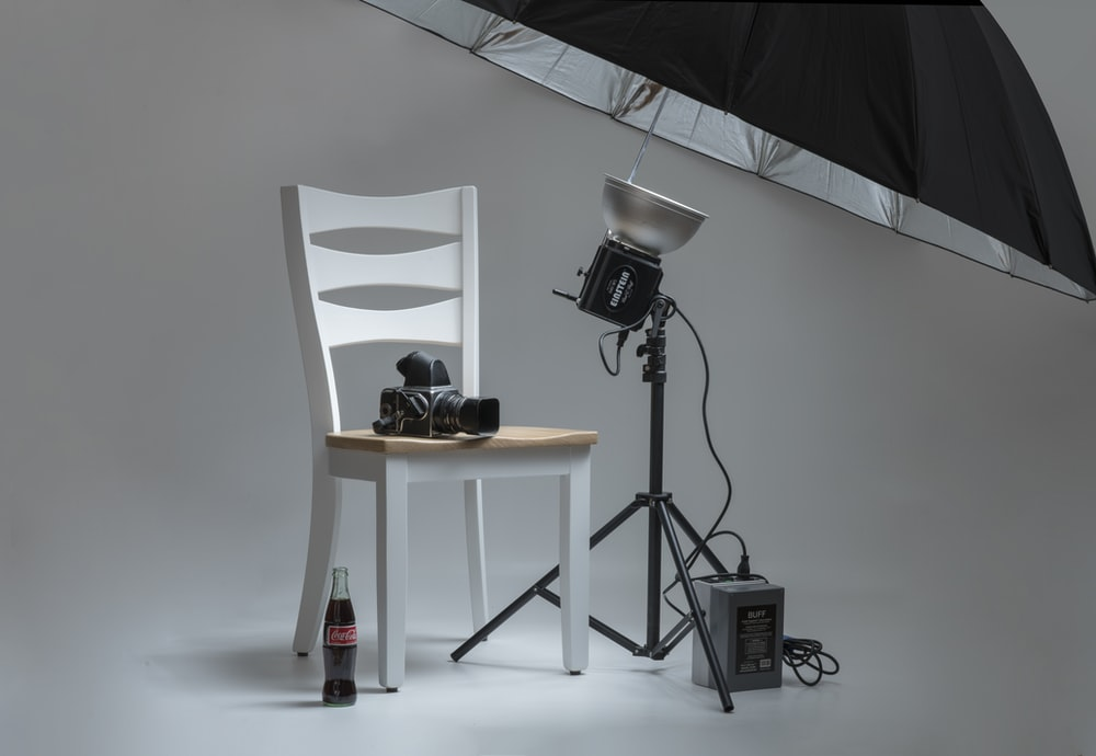 black video camera on white wooden chairs beside photo shooting umbrella