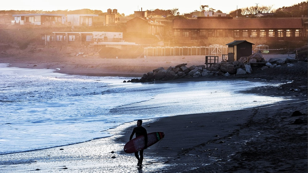 silhouette of man holding surfboard walking on shore during daytime