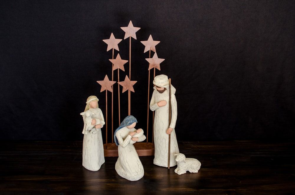 three religious figurines on brown surface