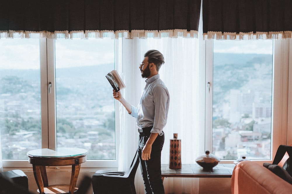 standing man reading book near window