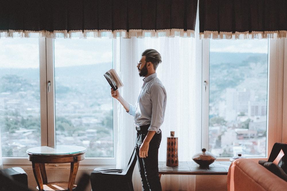 standing man reading book near window
