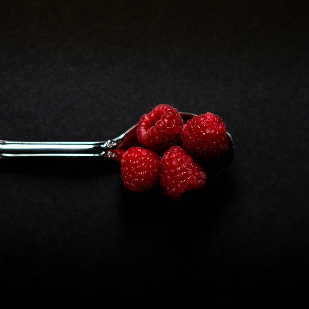 four Strawberry fruits on stainless steel spoon