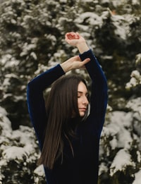 woman closing both eyes while raising both hands