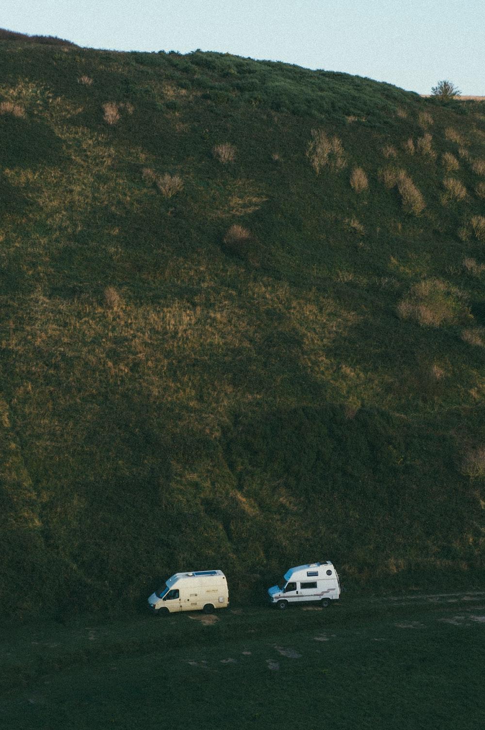 two white vans under mountain