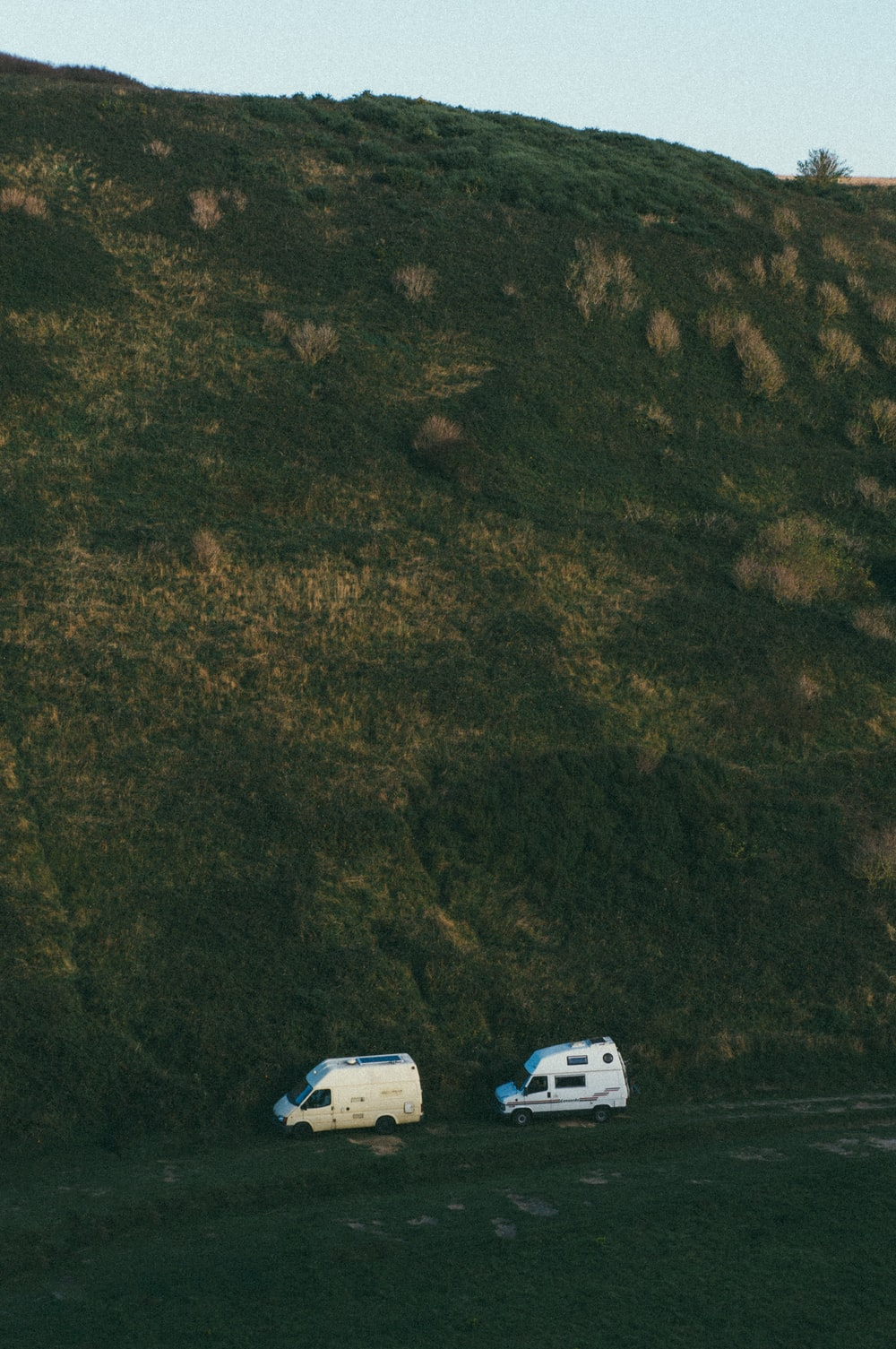 two white vans under mountain