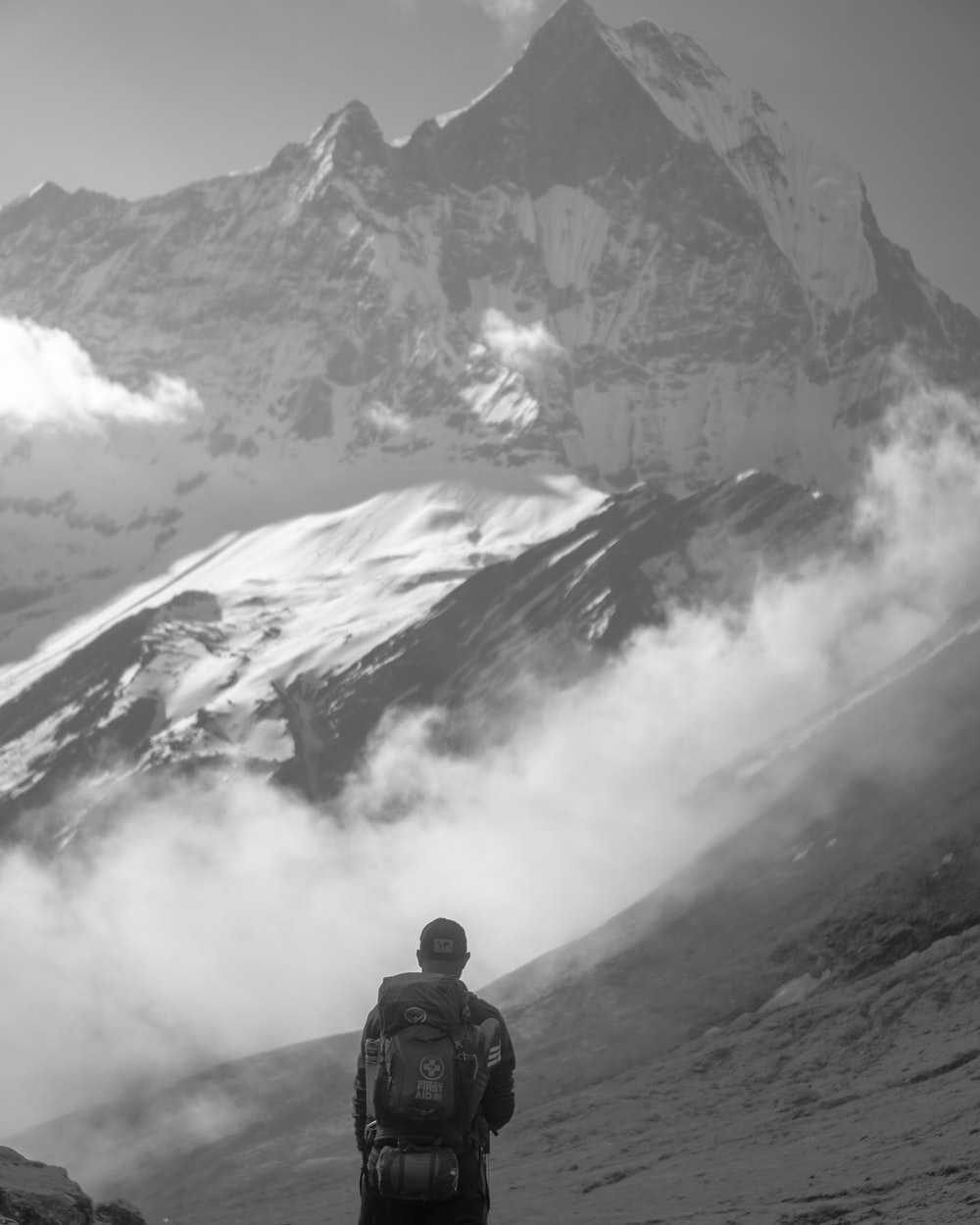 grayscale photography of man standing front of mountain