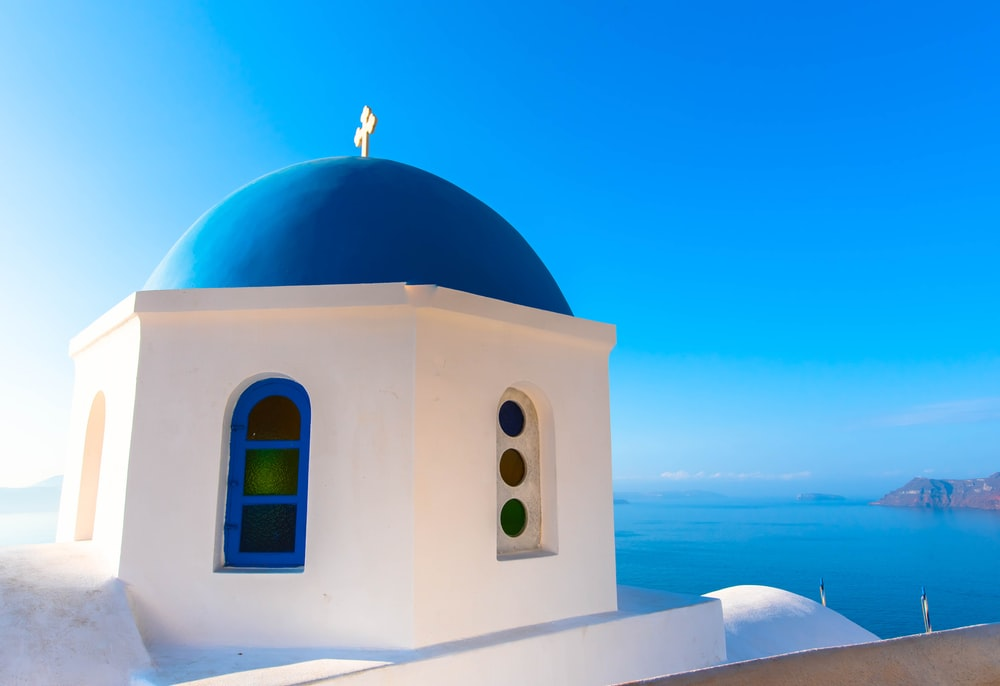 white and blue dome building beside sea