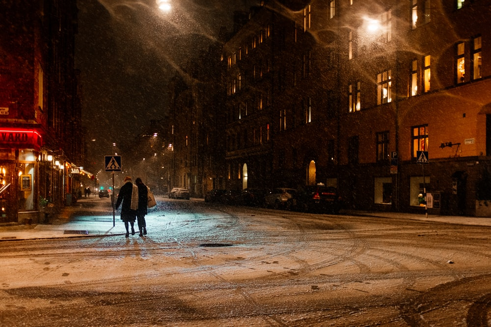 two person walking on street at night