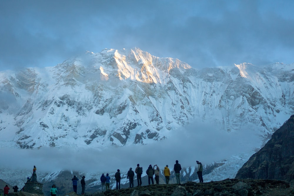 people on mountain with snow-covered mountain during daytime