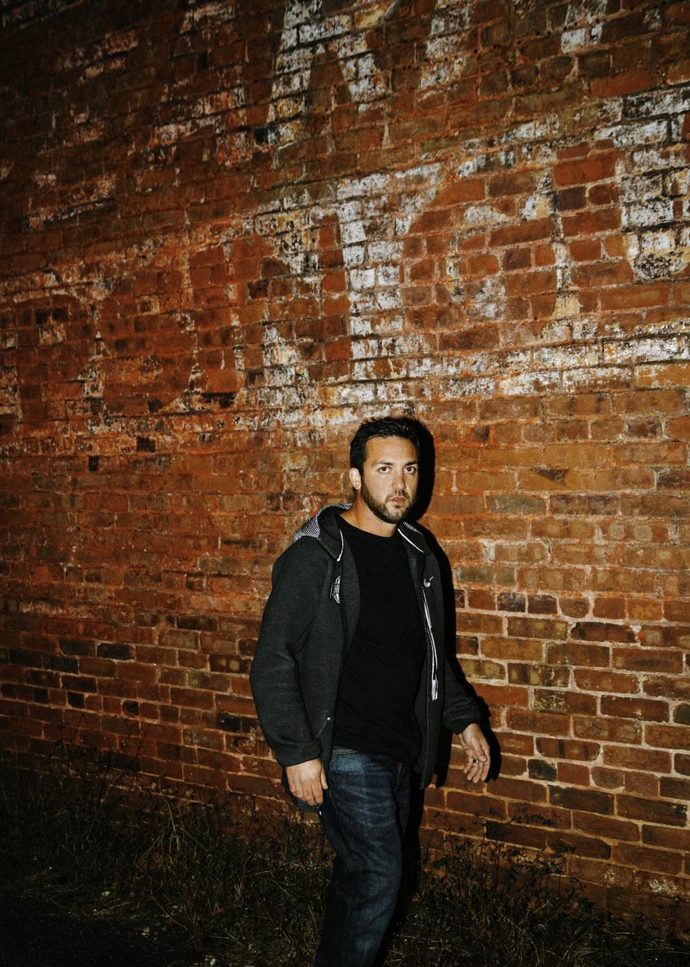 man in black zip-up hoodie walking beside brown bricked wall