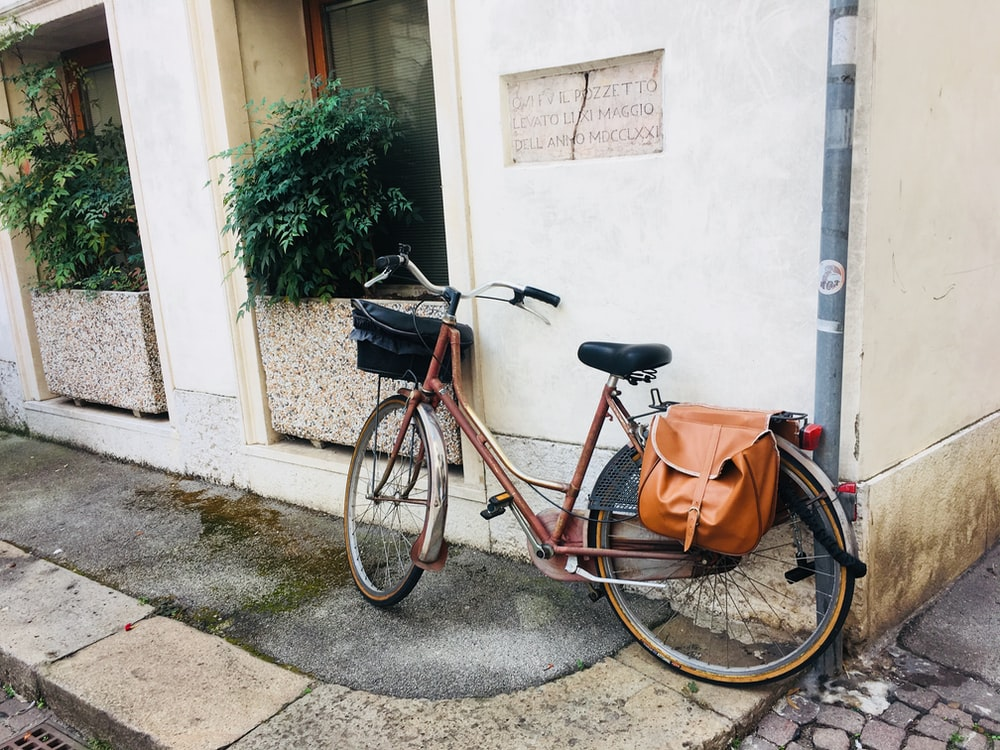 red bike with brown leather saddle bag parked beside white wall during daytime