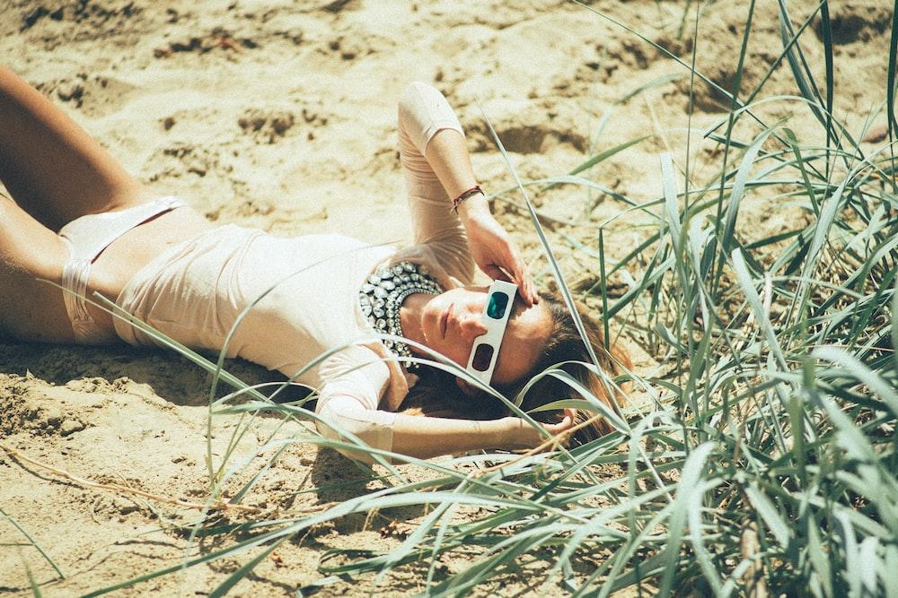 woman lying near green grass