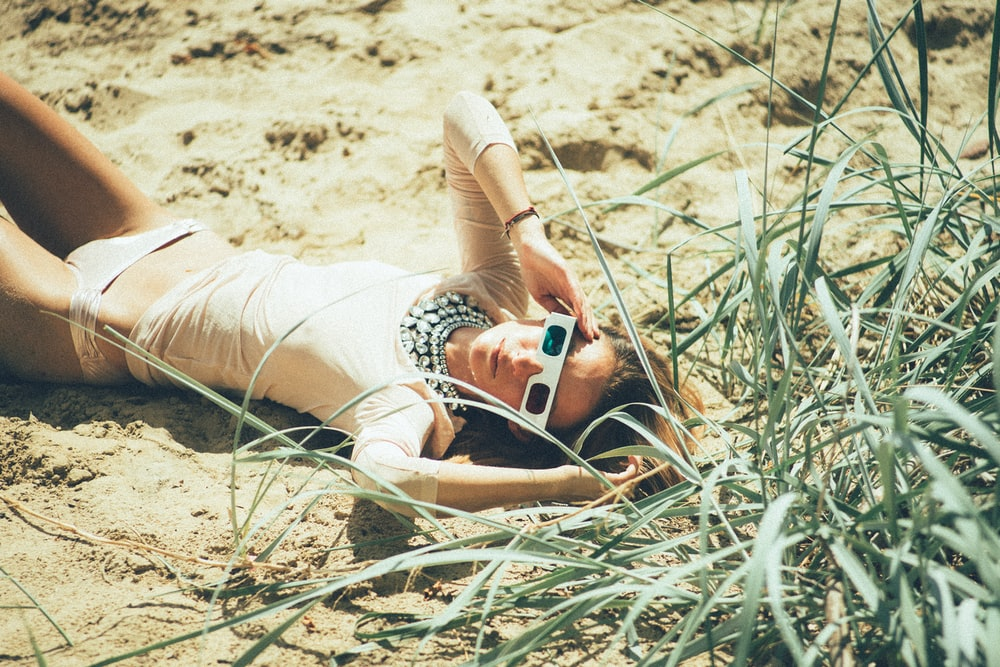 woman lying near green grass