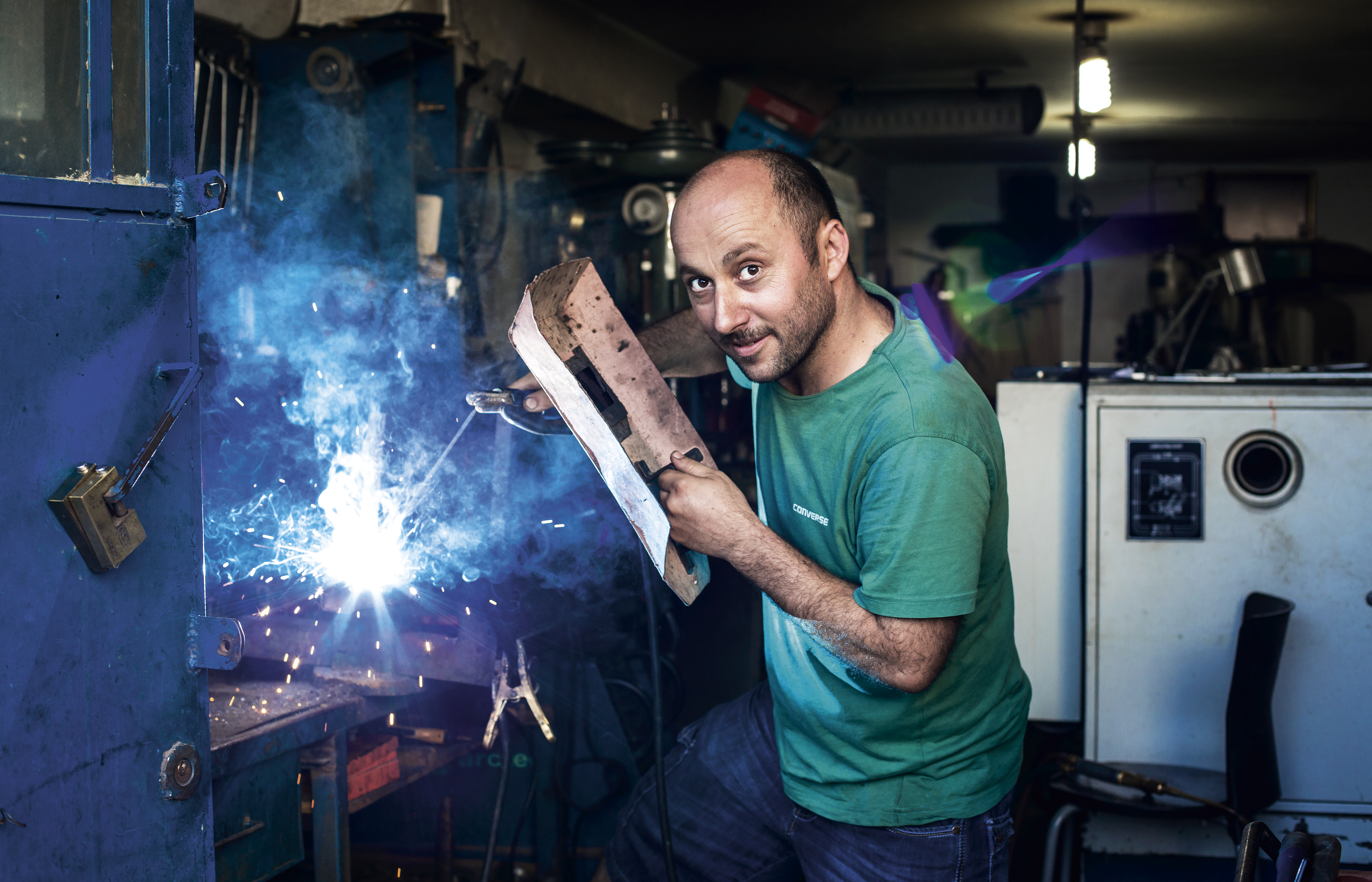 A welder doing his work, in an industrial place, a factory.