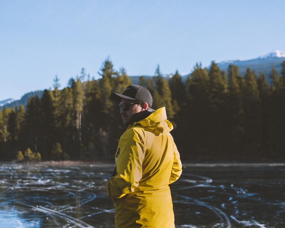 man wearing yellow jacket standing near body of water during daytime