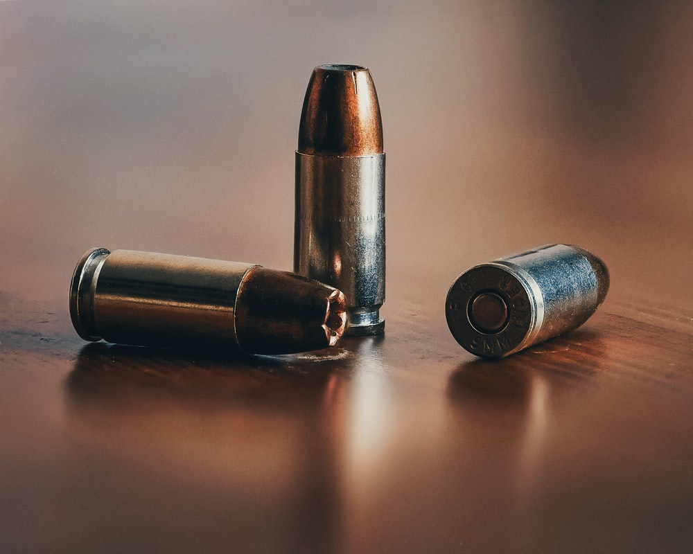 three gray bullets on brown surface