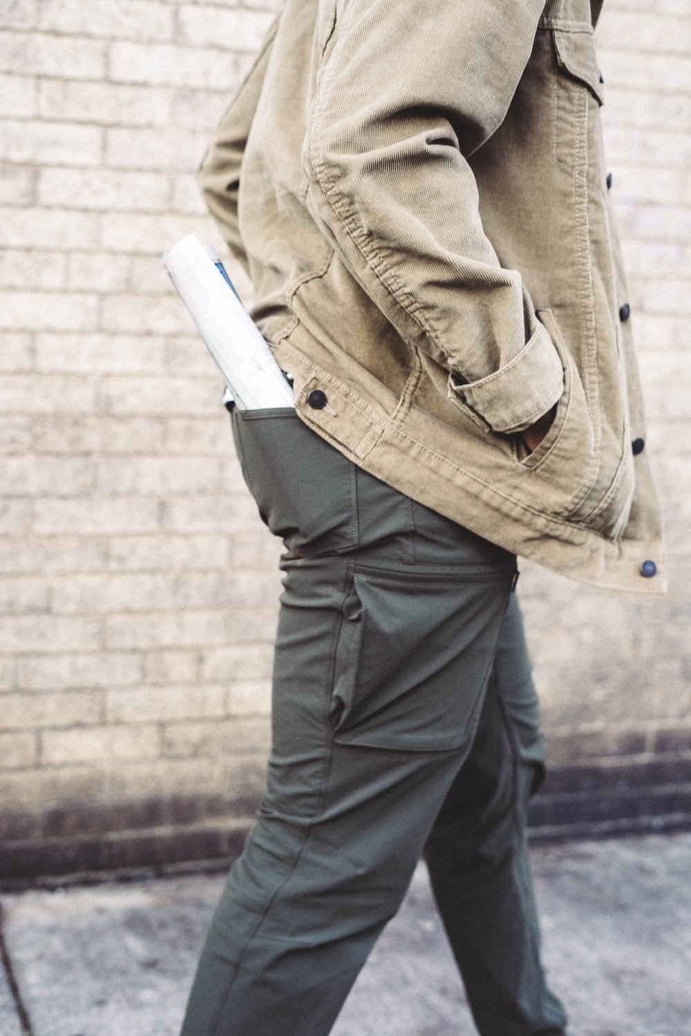 man walking hand on jacket's pocket with rolled paper on pants back pocket